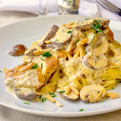 Creamy Dijon Chicken Linguine close up phot of single serving on a white plate