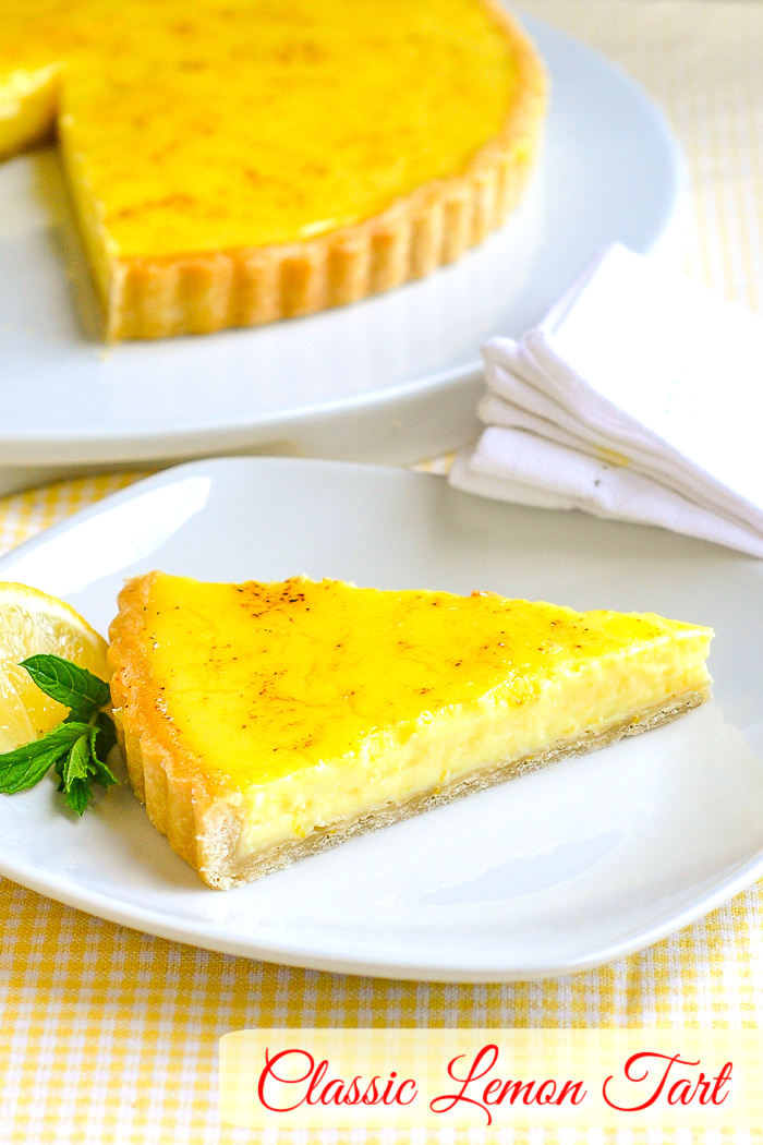 Photo of one slice of classic lemon tart on a white plate with mint and lemon garnish and title text added for Pinterest