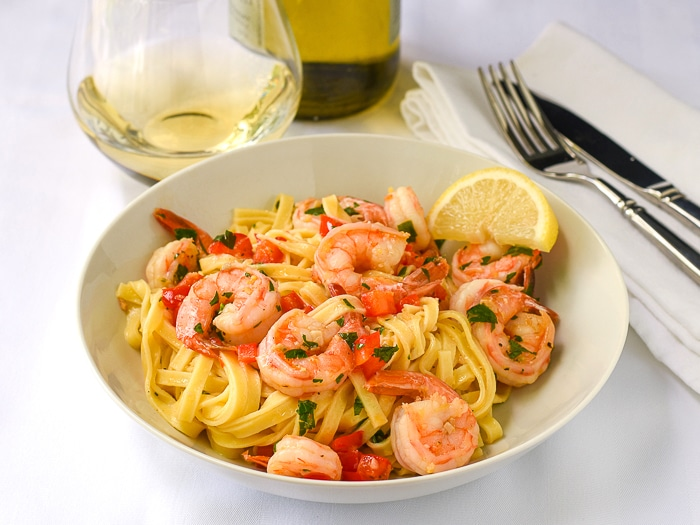 Super Simple Shrimp Scampi wide shot photo of a single serving in a white bowl with wine in background