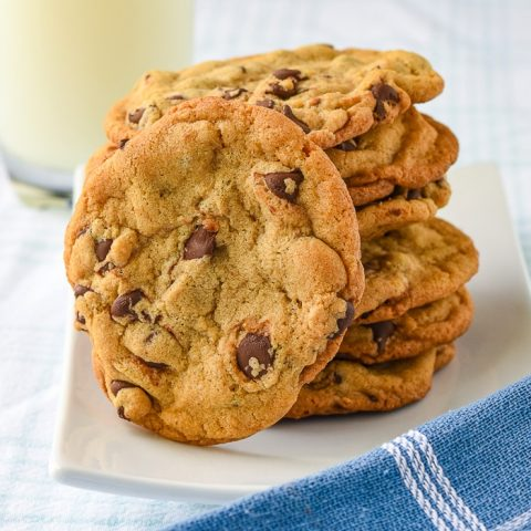 The Best Chocolate Chip Cookies photo of stacked cookies on a white plate with a glass of milk in the background