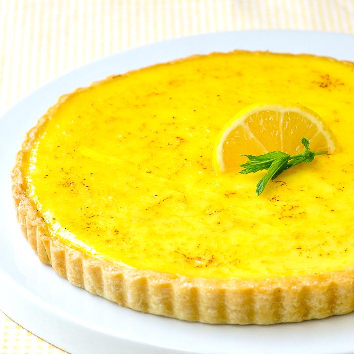 Uncut classic lemon tart on a flat white plate