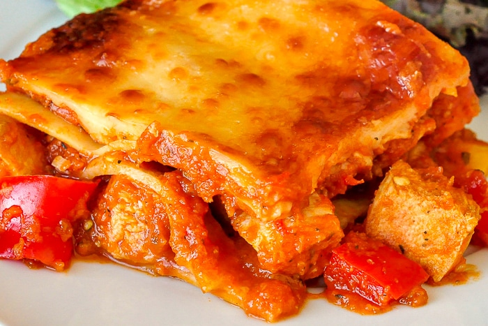 Chicken Parmesan Lasagna close up photo of single serving on a white plate