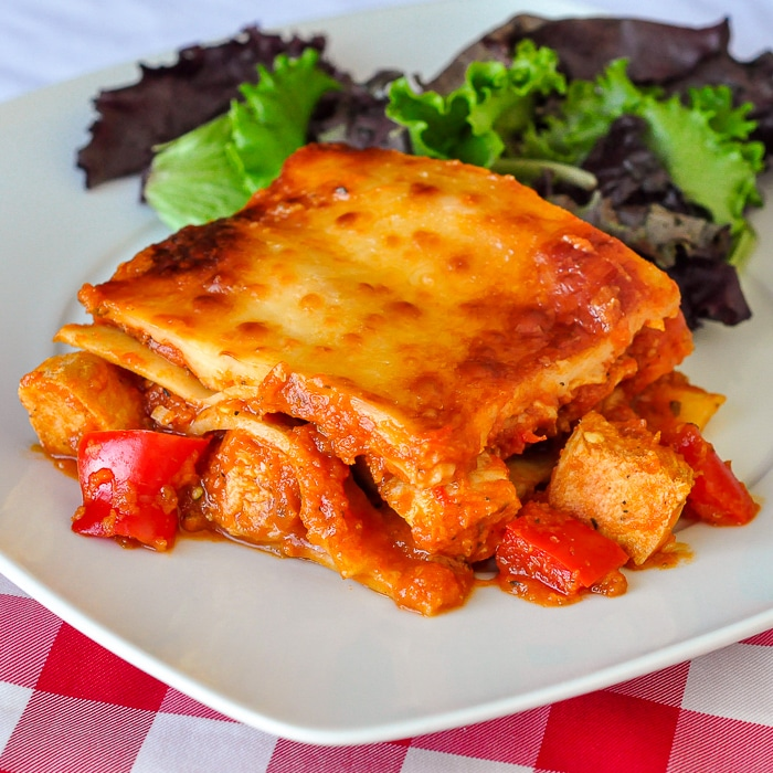 Chicken Parmesan Lasagna photo of single serving with salad on a white plate.