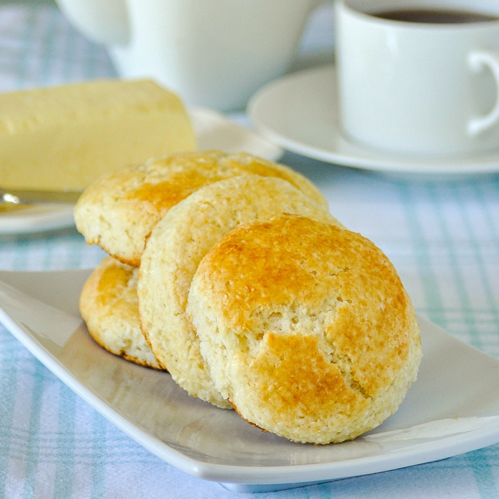 Coconut Tea Buns on a white plate with coffee service in the background