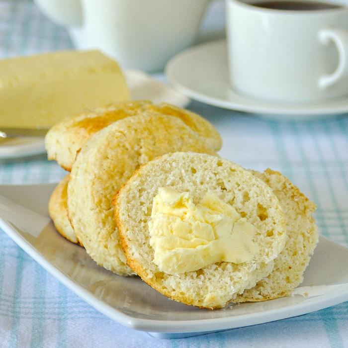 Coconut Tea Buns photo of butter spread on a tea bun cut in half