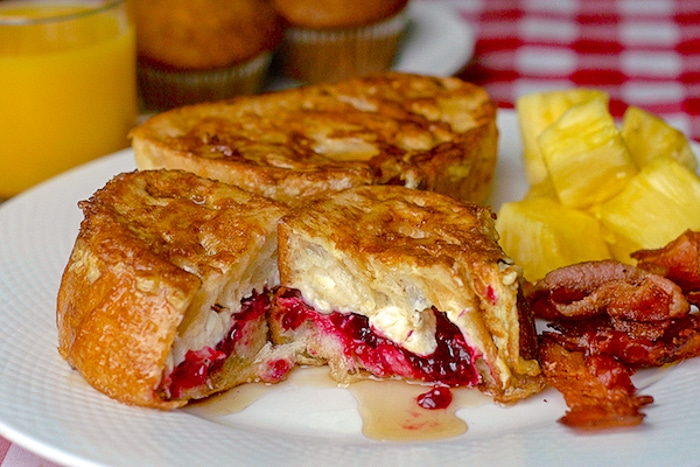 Partridgeberry Cream Cheese Stuffed French Toast on a white plate with bacon and fruit
