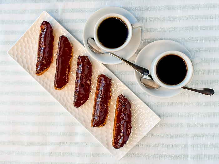 Overhead photo of chocolate dipped Almond Raisin Biscotti with 2 cups of espresso