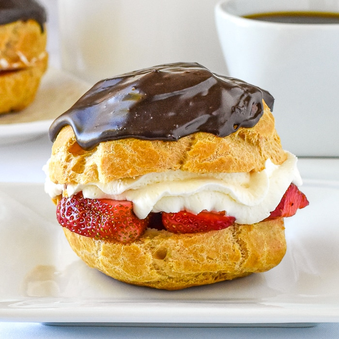 Strawberry Chocolate Custard Cream Puffs close up featured image of a single cream puff