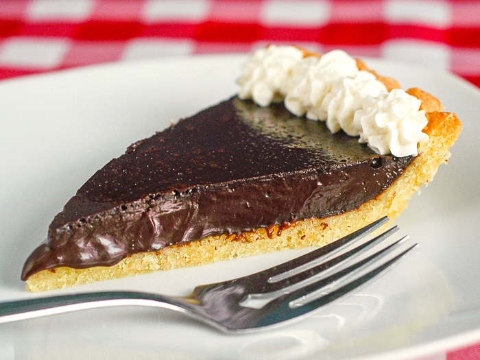 Tarte au Chocolat photo ofsingle slice garnished with whipped cream on a white plate