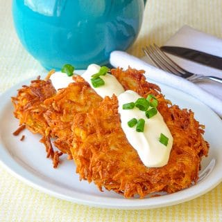 Garlic Parmesan Potato Latkes shown on a white plate with a dollop of sour cream