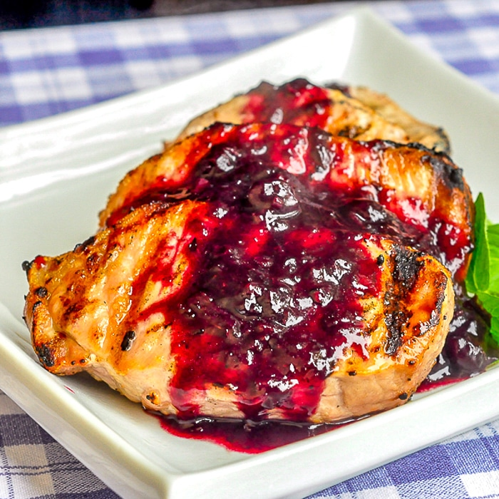 Blueberry Balsamic Pork Chops on a white serving platter with herb garnish