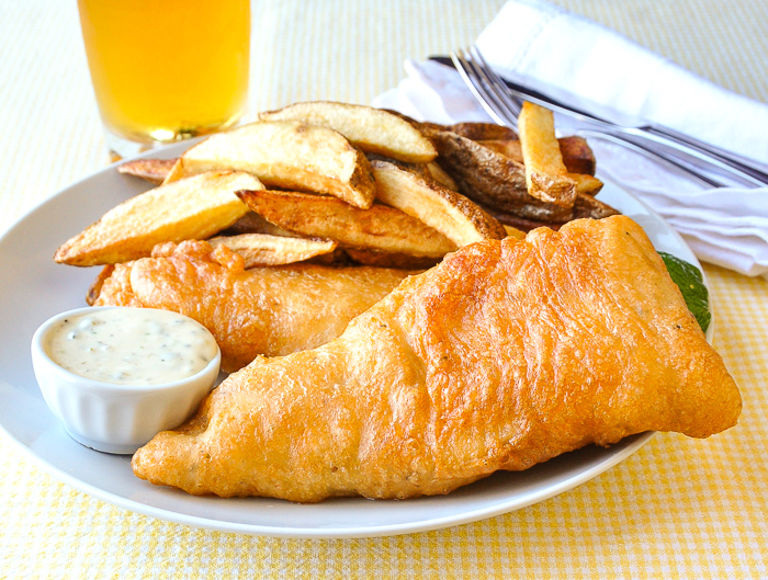 Fish and chips shown with tartar sauce and a glass of beer in the background