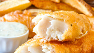 Super Crispy fish and chips close up photo of one piece of cooked fish broken open to reveal interior