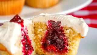 Vanilla Buttercream Cupcakes close up photo of one cupcake revealing the jam centre