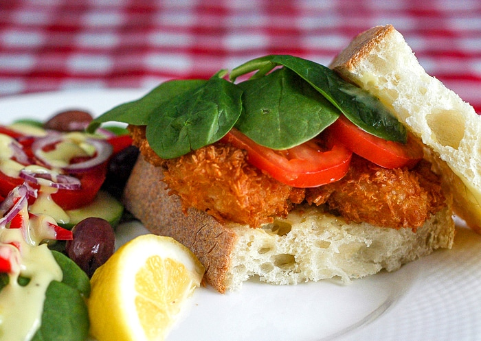 Coconut shrimp sandwich on a white plate with salad on the siide.