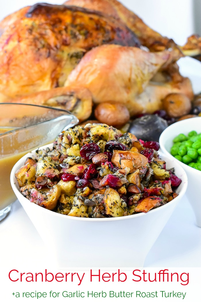 Herb Cranberry Stuffing shown with turkey dinner dishes in the background and title text added for Pinterest