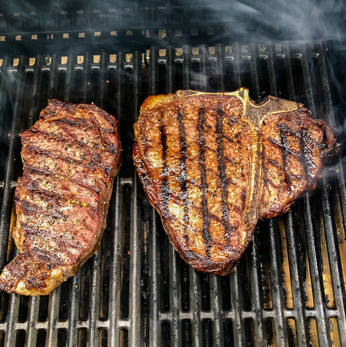 photo of a t bone steak and a prime rib steak on a gas grill