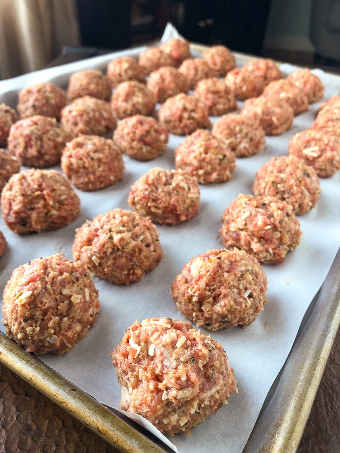 Italian Sausage Meatballs on a parchment paper baking sheet ready for the oven