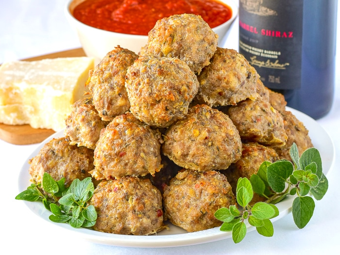 Italian Sausage Meatballs on a white plate with wine and parmesan cheese in background