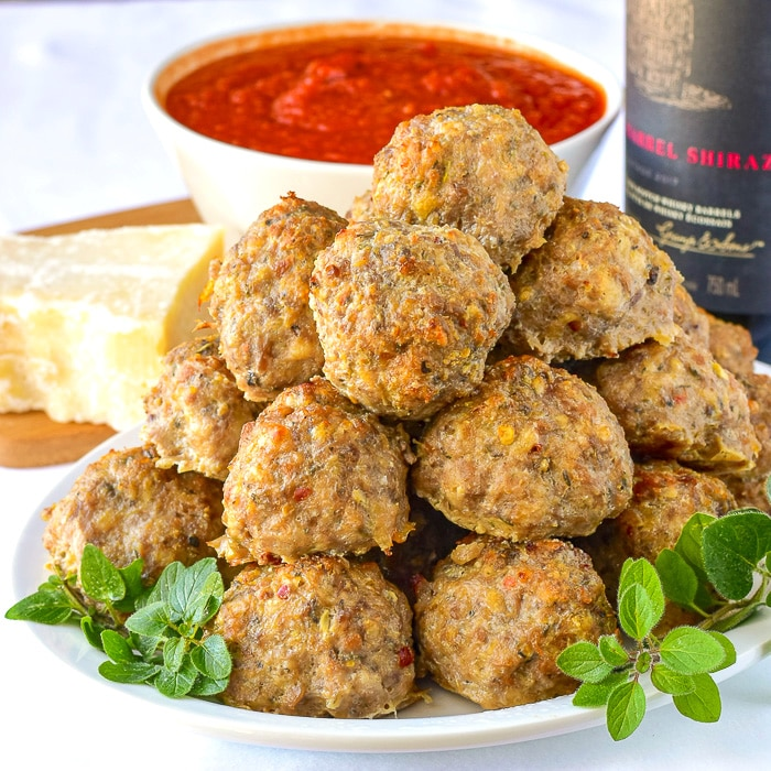 Italian Sausage Meatballs stacked on a white plate garnished with oregano.