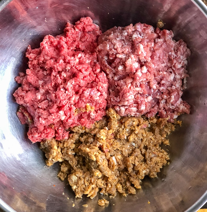 Italian Sausage meat, ground beef and ground pork in a stainless steel bowl