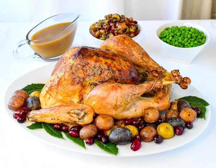 Overhead photo of finished turkey on a white platter with herb cranberry stuffing, gravy and peas