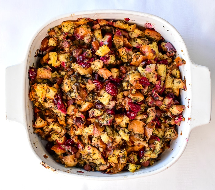 Overhead shot of herb cranberry stuffing in a white casserole dish
