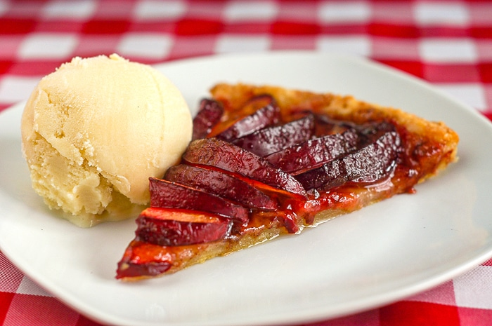 Single slice of plum tart with scoop of gelato on a white plate