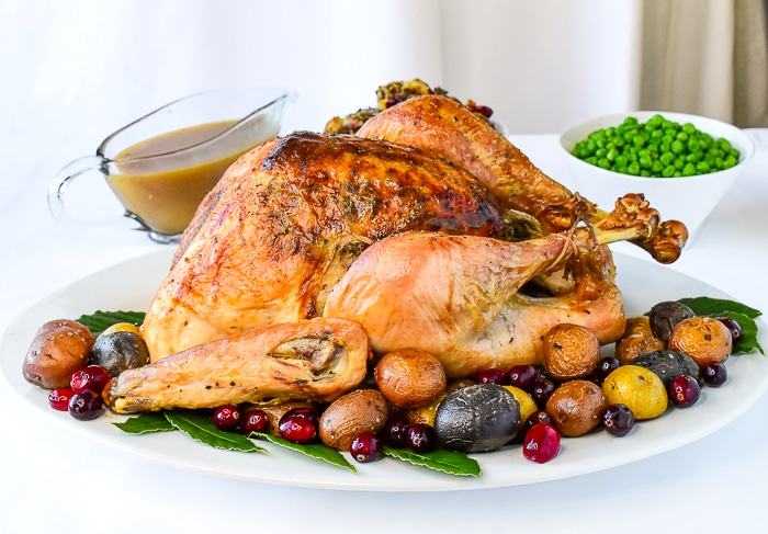 Turkey on a white platter surrounded by roasted potatoes and cranberries