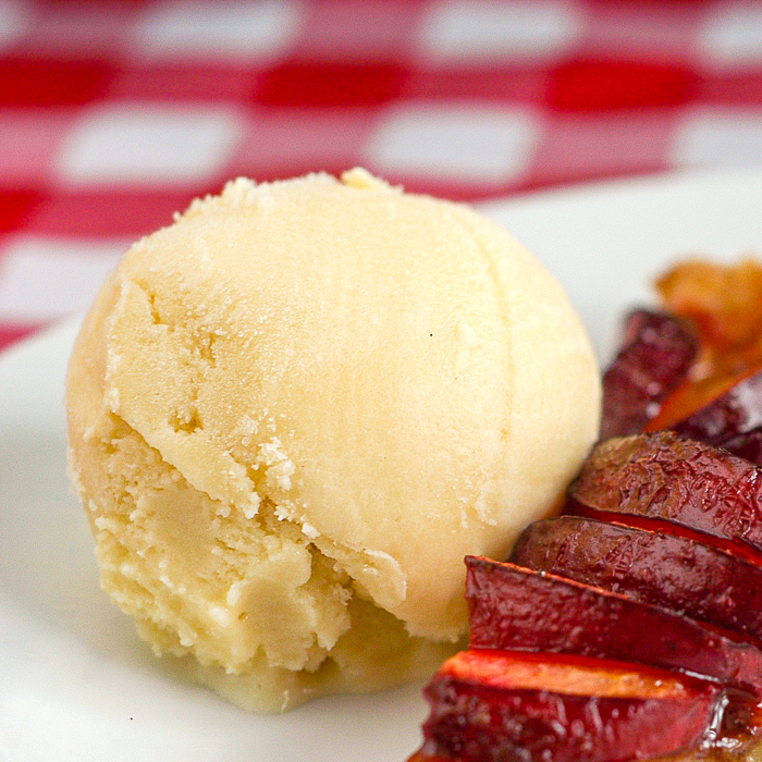 Vanilla Gelato on a white plate with a slice of plum tart.