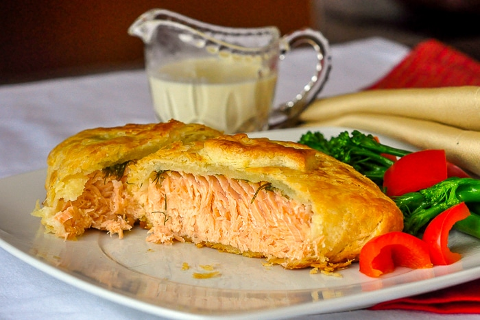 Salmon in pastry wide shot photo with vegetables on a white plate