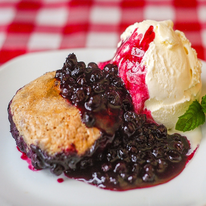 Cinnamon Biscuit Blueberry Cobbler photo of a single serving with vanilla ice cream on a white plate