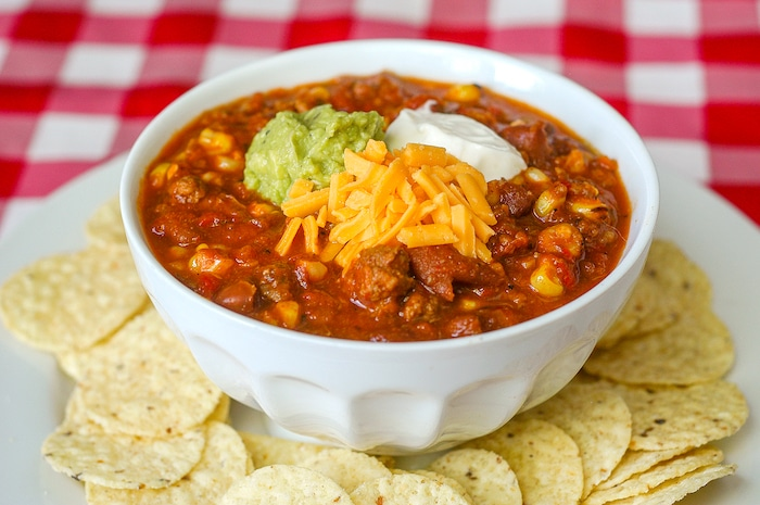 Grilled Corn Sausage Chili pictured in a white bowl surrounded by tortilla chips.