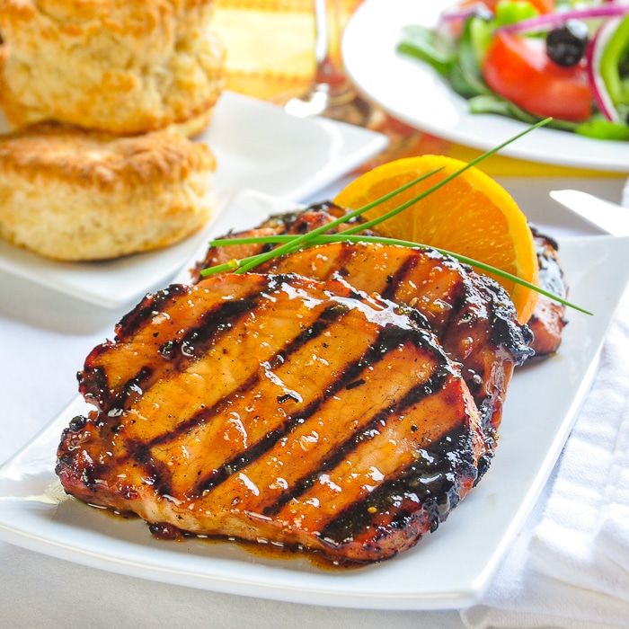 Orange Glazed Pork Chops with Cardamom and Honey close up photo of grilled and glazed chops on a white platter
