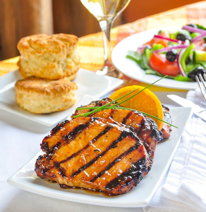 Orange Glazed Pork Chops with Cardamom and Honey shown on a white platter with biscuits and salad in the background