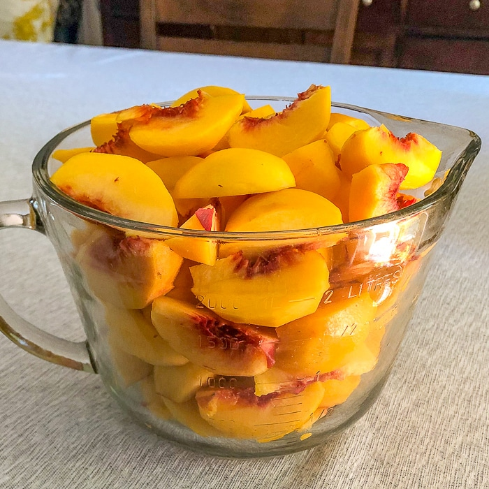 Peach wedges in glass measuring bowl for Peach Crumble