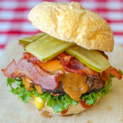 Bacon Sundried Tomato Burgers photo of burger on a wooden cutting board