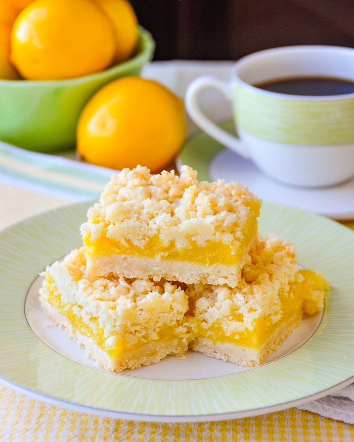 Coconut Lemon Crumble Bars shown with coffee and fresh bowl of lemons.