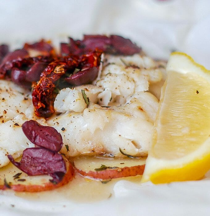 Newfoundland Cod with Olives and Sundried Tomatoes en Papillote showing open parchment paper packet