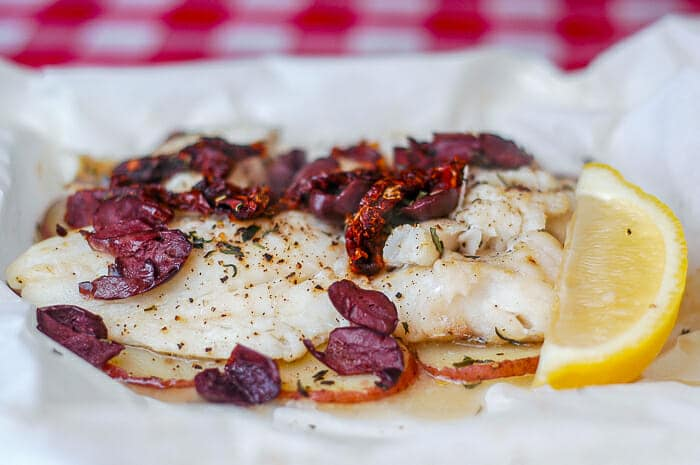 Newfoundland Cod with Olives and Sundried Tomatoes en Papillote with lemon wedge