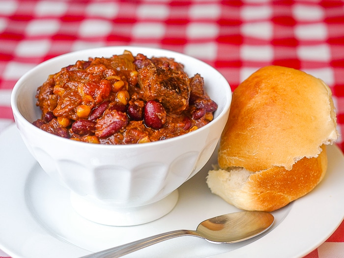 Beef Bacon Bean Stew photo of a single serving on a white plate with a fresh bread roll on the side