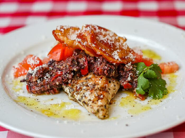 Garlic Oregano Chicken with Red Pepper Parmesan Tapenade and Crispy Pancetta shown plated.