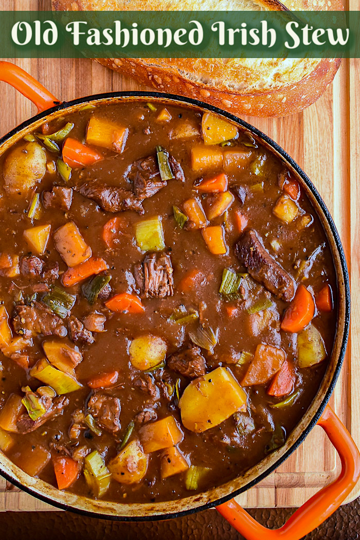 Irish Stew in an orange dutch oven with title text added for Pinterest