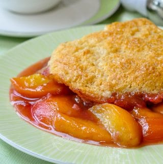 Peach Cobbler close up image of a single serving on green plate