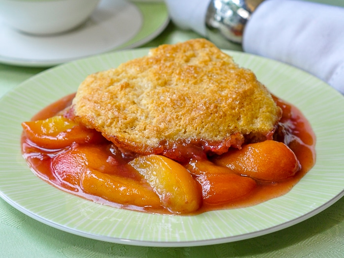 Peach Cobbler wide shot image of a single serving on green plate