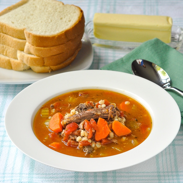 one bowl of Beef Barley Soup with Tomatoes with bread and butter in the background