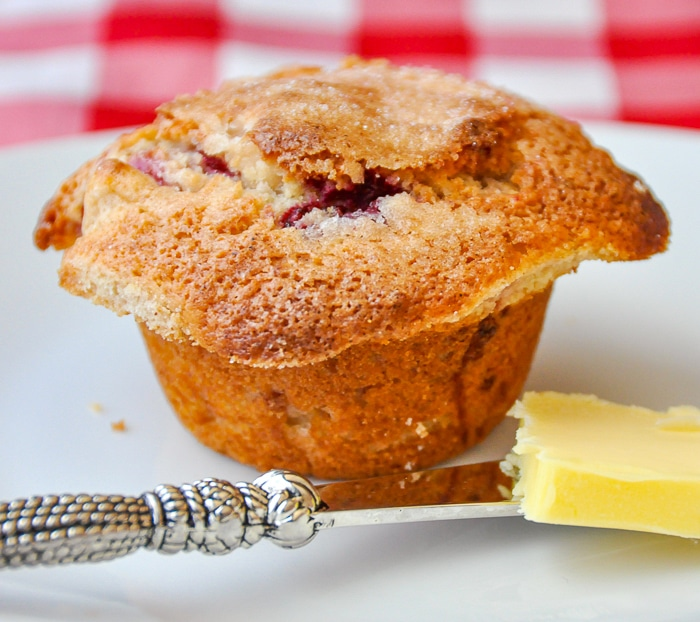 Apple Raspberry Muffins photo of one muffin on a white plate with butter knife