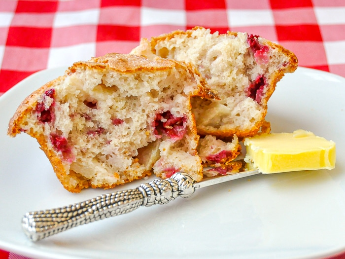 Apple Raspberry Muffins wide shot photo of one muffin on a white plate with butter knife
