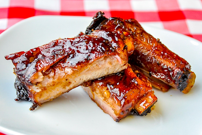 Black Bean Ginger Glazed Ribs on a white plate with red checkered tablecloth background