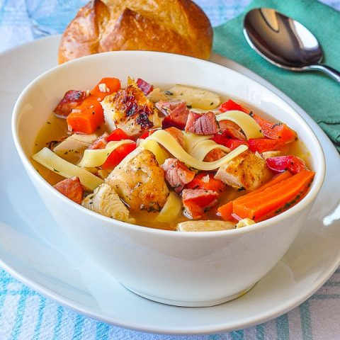Chorizo Rotisserie Chicken Noodle Soup photo of a singe serving in white bowll with a bread roll on the side